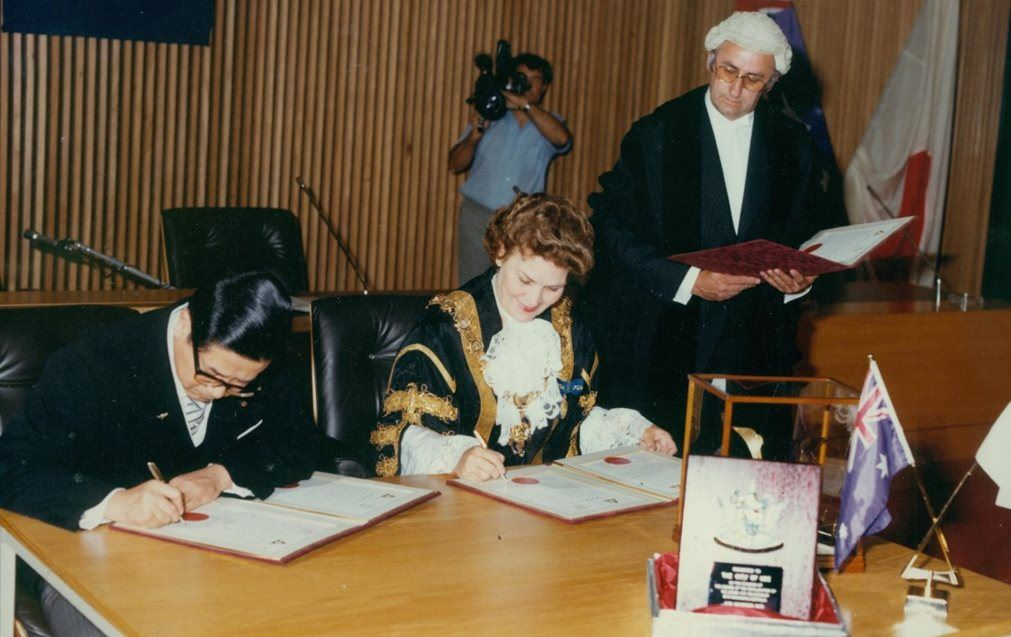 Mayor of Ube, Mr Hideo Futatsugi, and Newcastle Lord Mayor Joy Cummings sign the declaration while Town Clerk Barrie Lewis looks on.jpg